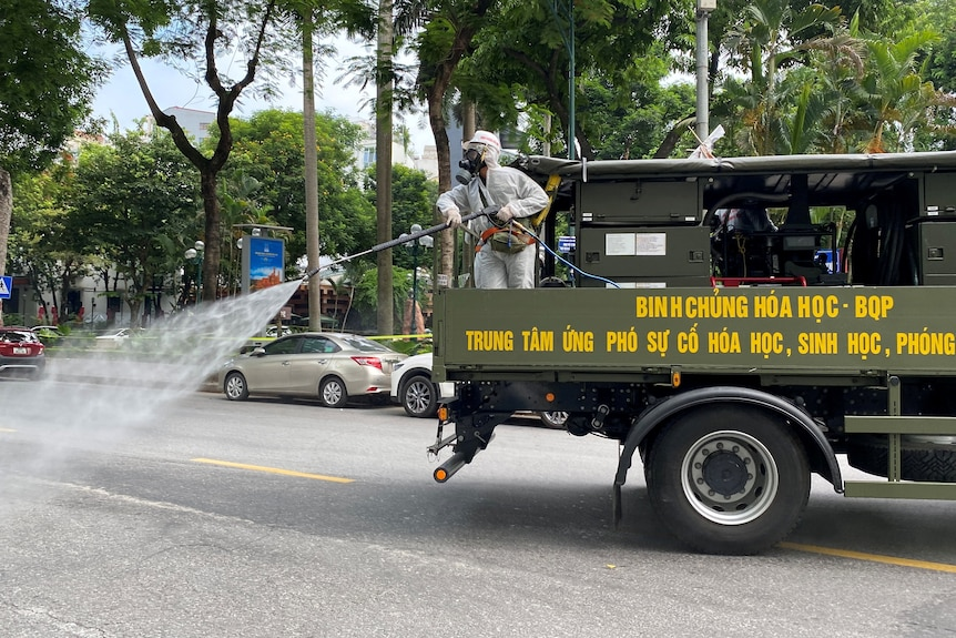 Military personnel wearing PPE spray disinfectant on the streets during a lockdown in Hanoi