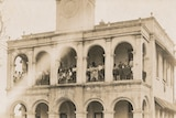 People stand on a balcony of a Town Hall