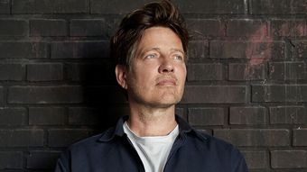 The director Thomas Vinterberg looking off to the side