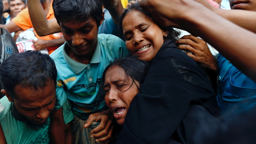 a woman makes an anguished cry as se is jostled in a crowd of people