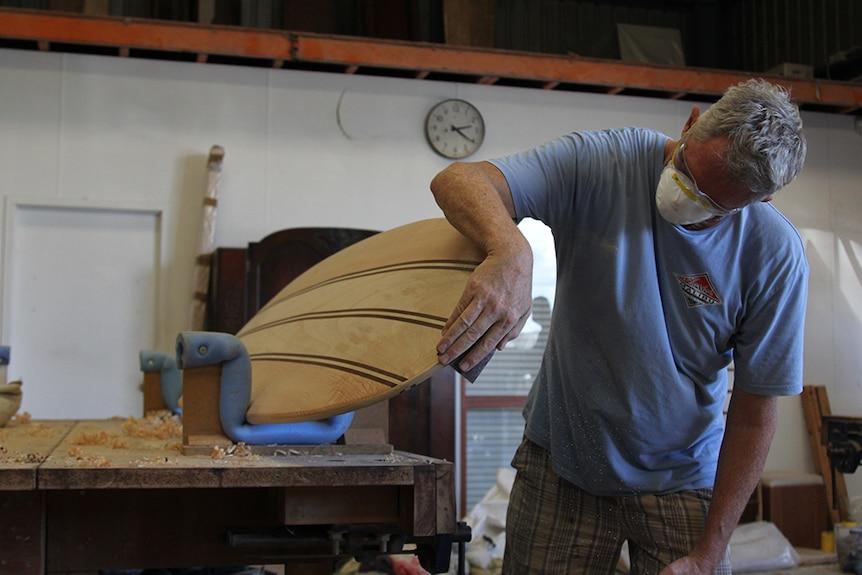 A man sanding a surfboard in a woodworking shop.