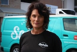 A woman in a black shirt stands in front of a blue van