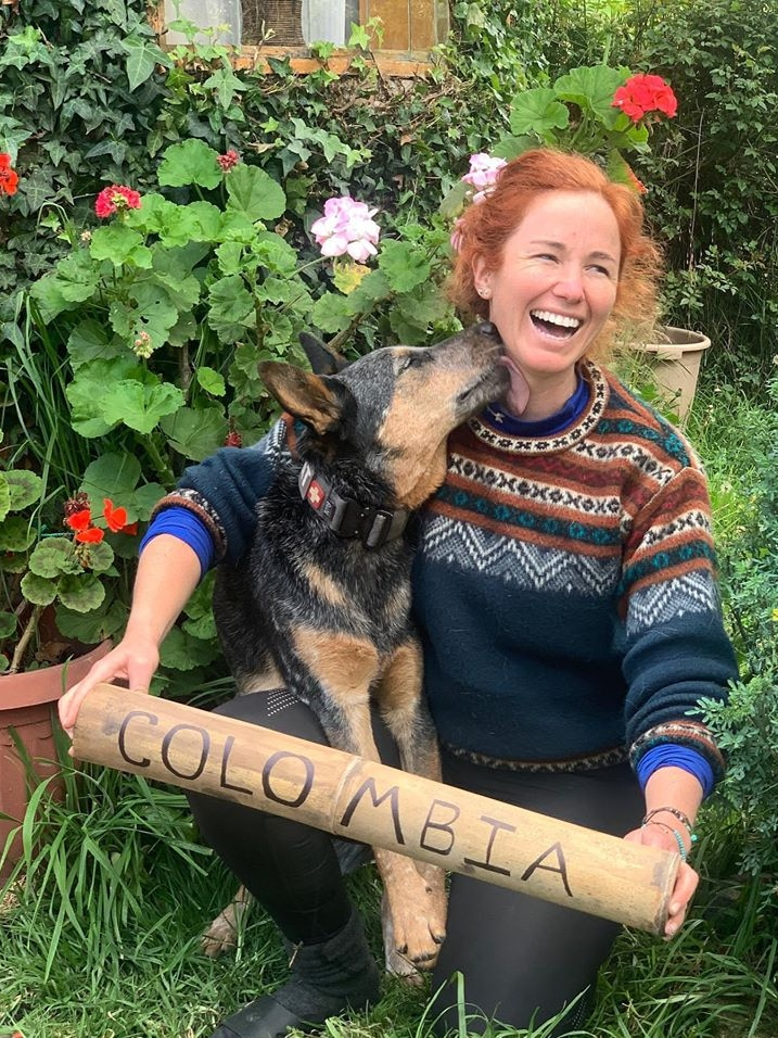 Lucy Barnard kneeling holding Colombia sign looking away from lens laughing as dog Wombat licks neck