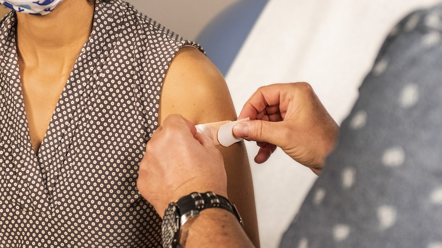 Bandaid being put on arm.