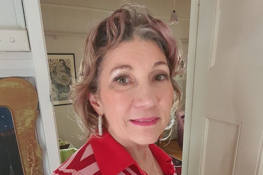 A woman in her 60s in a red striped shirt looking at the camera.