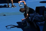 Alexander Zverev seated at the change of ends smashing his already broken racquet into the ground.