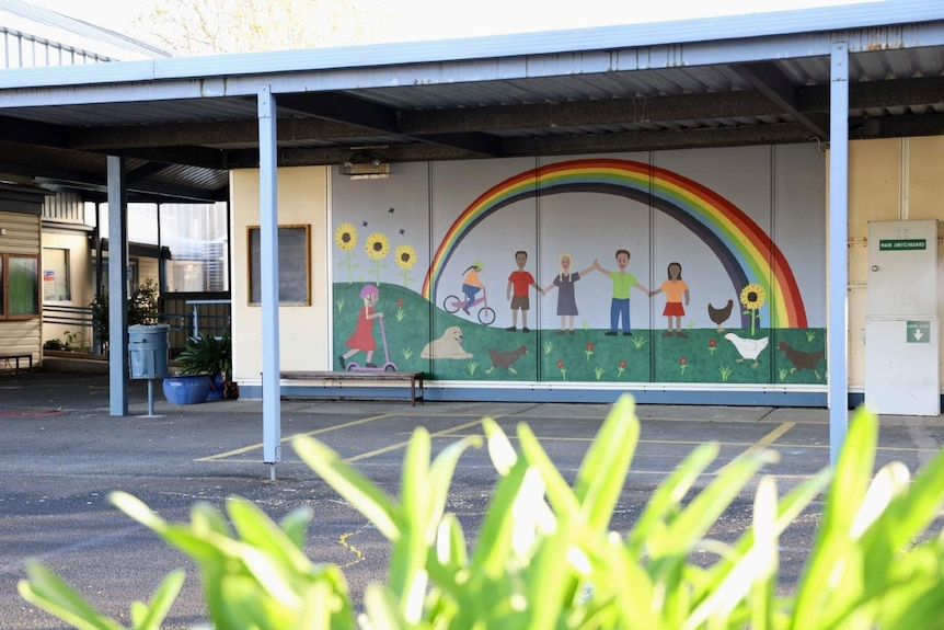 A mural with people painted under a rainbow holding hands sits under a shelter on school grounds.