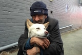 Homeless man hugs  pale coloured dog with golden ears.