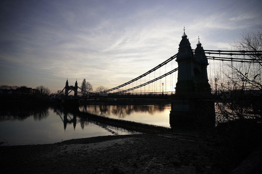 Hammersmith Bridge is reflected in the River Thames as the sun sets.