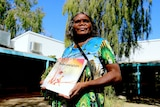 Alison 'Tjulapi' Carol holds a kids book called Tjulpu and Walpa