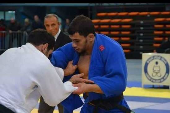 A judoka in a blue outfit grapples with an opponent in a judo competition.