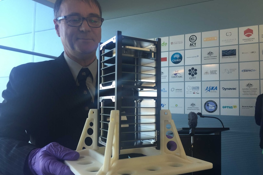 Professor Iver Cairns of University of Sydney holding one of the Australian made cube satellites