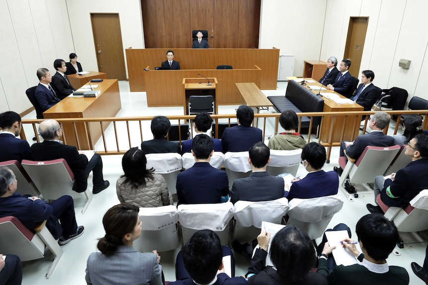Judge Yuichi Tada, top center, and spectators sit in a courtroom ahead of Carlos Ghosn's court hearing.