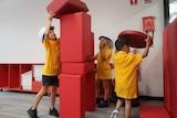Three children stack large red building blocks