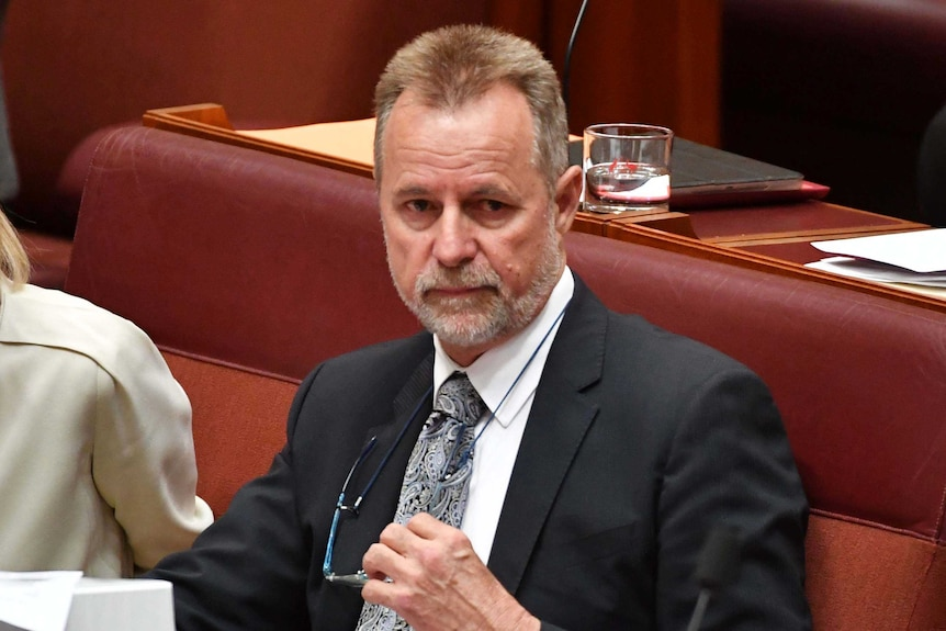 Nigel scullion removes his glasses in the senate chamber