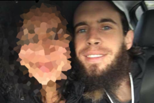 Damien Featherstone poses with another person, whose face is pixelated.