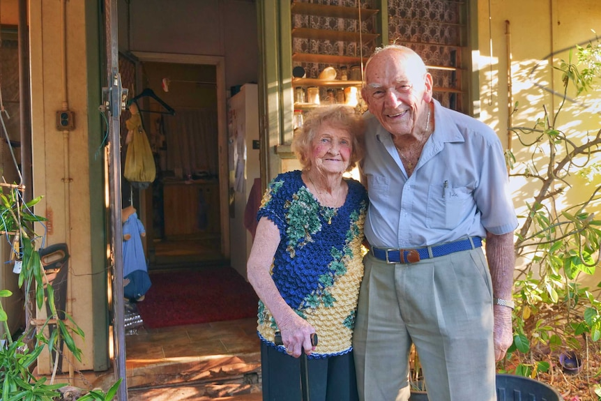 An elderly couple stand in front of their home.