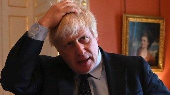 Boris Johnson runs his hands through his hair