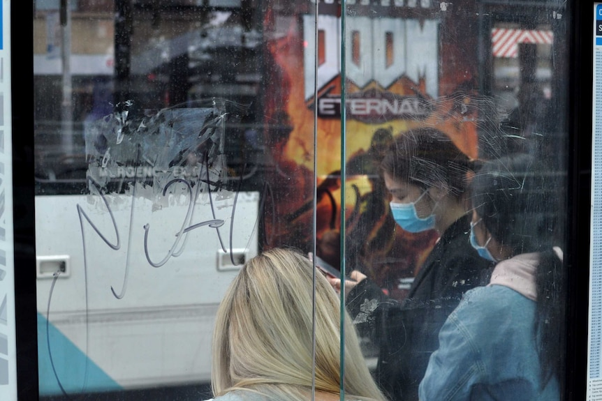 Two women wearing face masks stand at a bus stop. Behind them is a bus poster with the word 'Doom' in large letters.