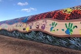 A large pipeline painted black with red, orange and yellow dots as well as colourful handprints.