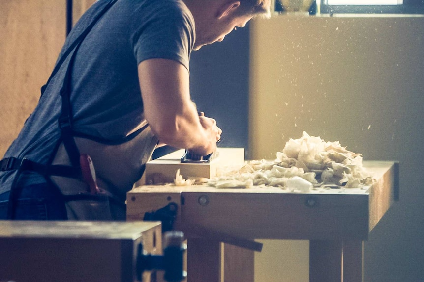 A man sanding a table with his back to the camera