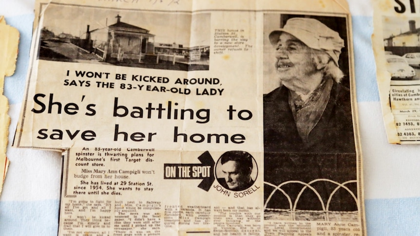 A photograph of a faded black-and-white newspaper clipping headlined 'She's battling to save her home'