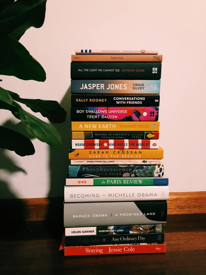 A large but neat pile of books stacked on a bench next to a houseplant.