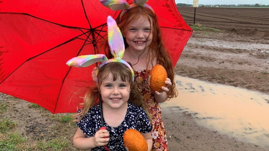 Two girls stand under an umbrella in Bundaberg