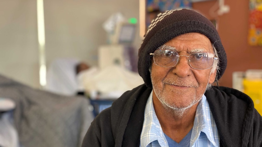 A man in glasses looks down the camera with a slight smile wearing a beanie and blue shirt