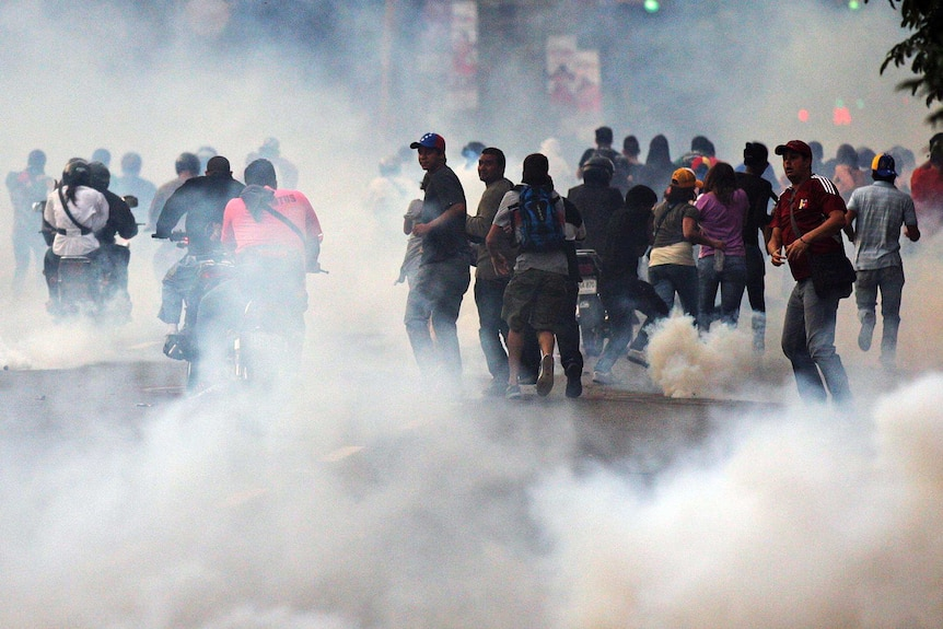 Supporters of Henrique Capriles run from tear gas.