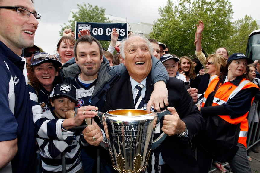 Frank Costa the president of the 2007 AFL premiers holds the cup with fans crowding around during a street parade.