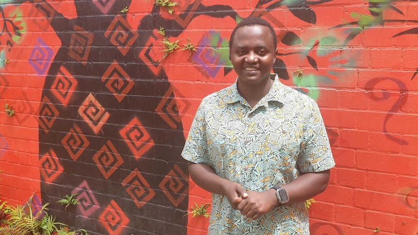 African man Iginas Gasengayire in front of a bright mural