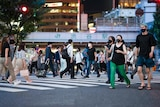 A crowded street crossing in Tokyo, with most pedestrians in masks.