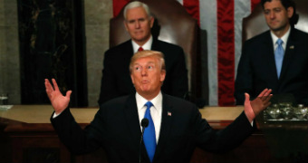 Donald Trump raises his arms, looks to the ceiling and pulls a coy face during the state of the union address