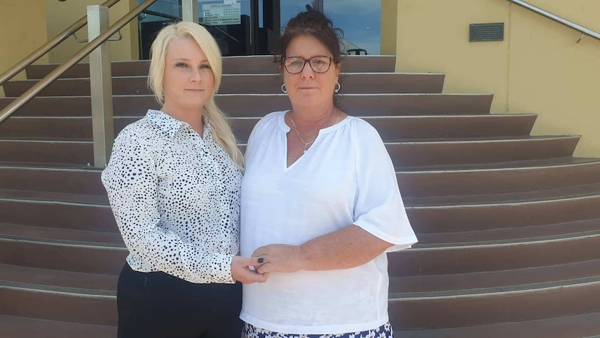 Two women stand outside the Mackay Court House holding each other as the look forward.