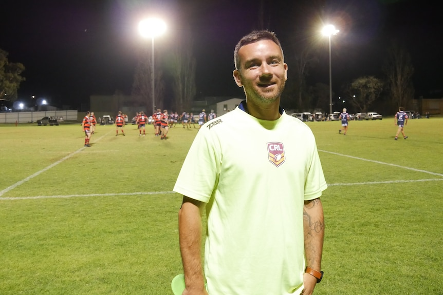 A middle-aged man wearing a fluro yellow t-shirt stands in front of a local footy game at night time