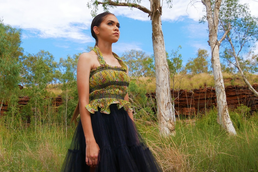 A young woman models a strappy green top and long black skirt amid tall grass, trees and red rocks.