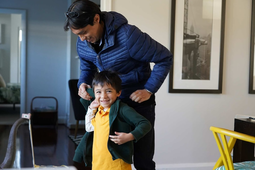A young boy smiling and putting his school jumper on stands alongside his dad as they get ready for school.