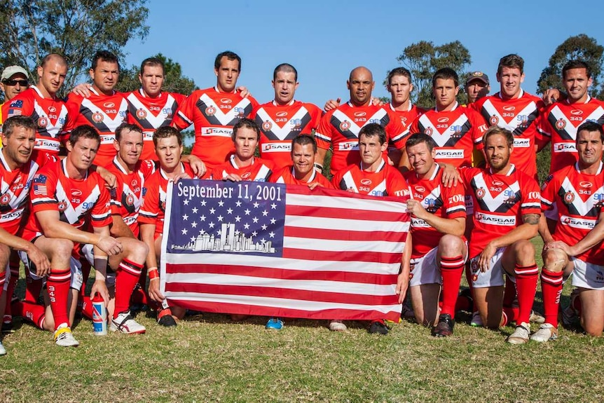 Players pose for a photograph with a US flag reading September 11 2001