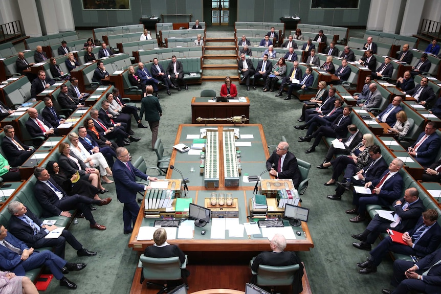 Politicians sit in their seats throughout the green House of Representatives chamber