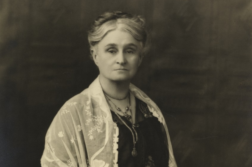 Old black and white photo of Edith Cowan, unsmiling, hair in a neat bun, wearing black dress with white lace shawl.