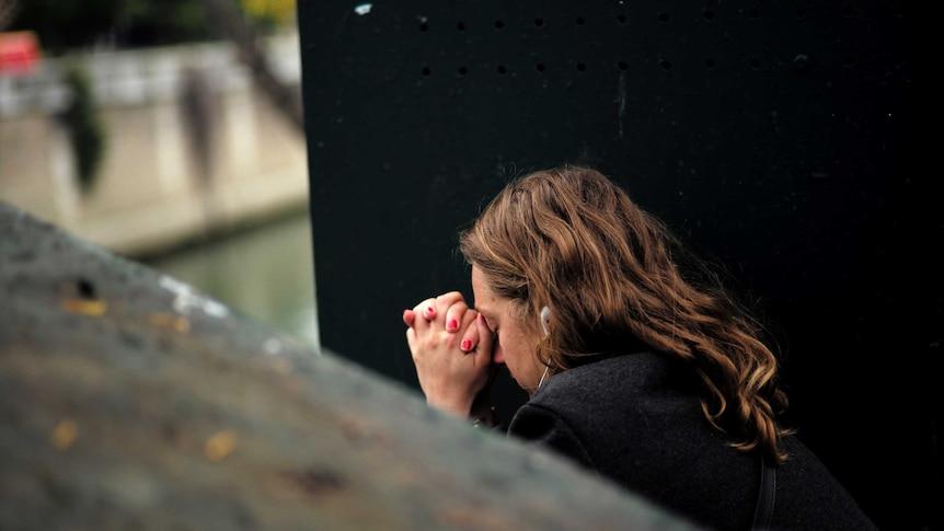 A woman prays by a river in Paris