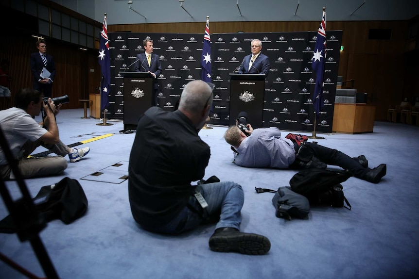 Photographers take photos of Scott Morrison and Dan Tehan, who are standing at separate podiums.