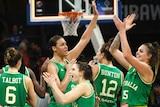 Women wearing green singlets high five each other