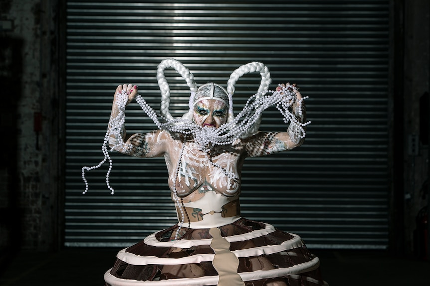 Colour photo of burlesque and performance artist Glitta Supernova performing on stage.