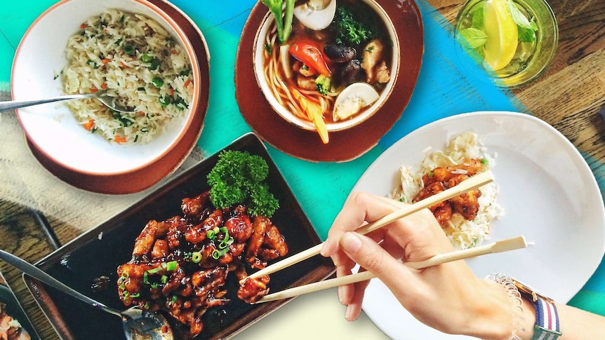 Bowls of tom yum soup, fried rice and marinated meat, with a hand using chopsticks to eat the Thai food.