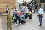 An army officer directs people from a bus into hotel quarantine.