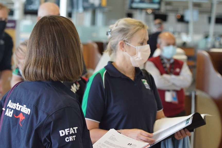 A woman in a face mask next to a woman in a blue shirt with 'Australian Aid' written on the back