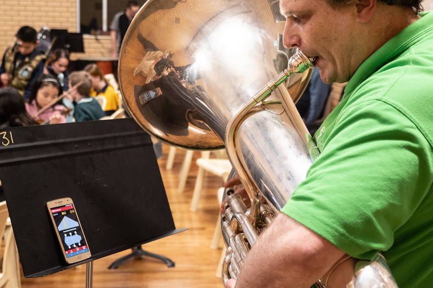 Troy Hawkins tunes his tuba before playing.