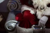 Santa's white-gloved hand rests on his red-suited knee
